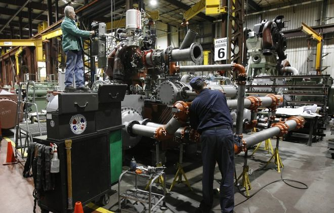 Workers assemble a giant compressor system at Cameron, before Ingersoll Rand acquired the facility. (News file photo)