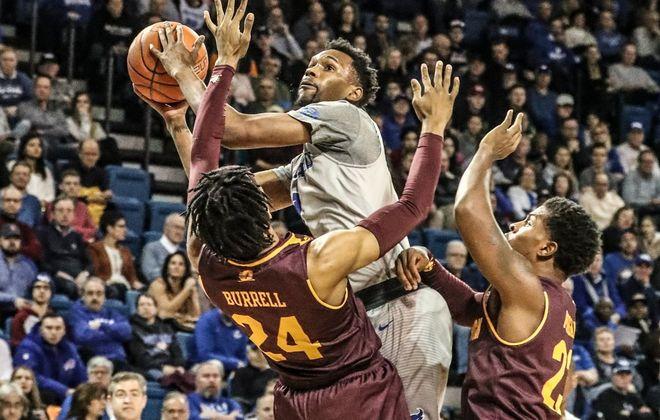University at Buffalo forward Montell McRae scores against Central Michigan forward Romelo Burrell  (James P. McCoy/News file photo)