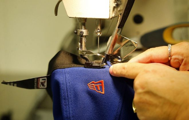 A worker sews a cap at the New Era plant in Derby. (Mark Mulville/The Buffalo News)