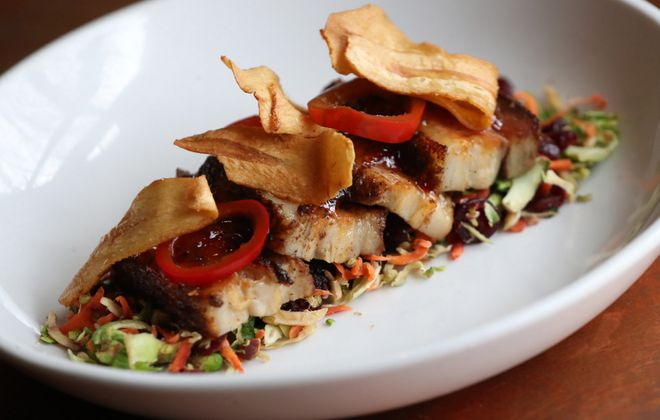 Shango's pork belly appetizer comes with brussels sprout carrot slaw, pepper jelly, pickled onions, and parsnip chips. (Sharon Cantillon/Buffalo News)