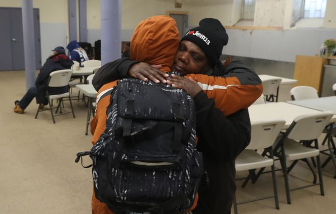 Charlene Mallory, an associate missionary at St. Luke's, gives a hug to a man seeking shelter from the cold during a Code Blue at St. Luke's Mission of Mercy. (John Hickey/Buffalo News file)