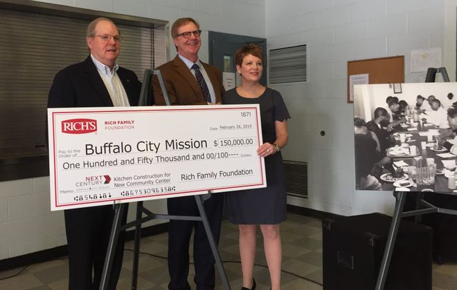 City Mission CEO Stuart Harper, Howard Rich of Rich's Products and City Mission Associate Executive Director Aubrey Calhoun hold the big ceremonial check from the Rich Family Foundation. (Keith McShea/Buffalo News)