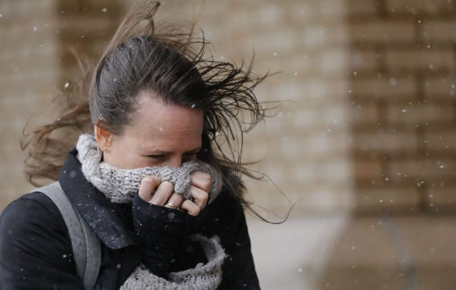 Shanon Jacobs of Amherst braces herself against the wind and snow as she walks down Main Street near her workplace, Wednesday, April 4, 2018. (Derek Gee/Buffalo News file photo)