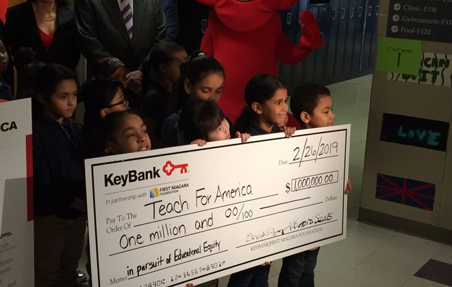 Students from Frank A. Sedita Academy display a ceremonial check Tuesday as KeyBank and the First Niagara Foundation announce a $1 million grant to Teach For America Buffalo. (Jay Rey/Buffalo News)