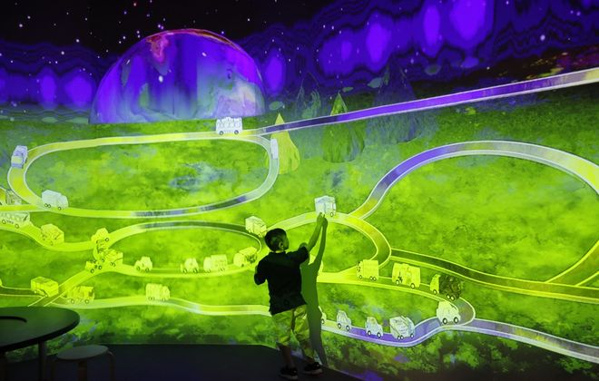 Nicholas Schaffer, 6 1/2, interacts with cars moving on a projected highway in an exhibit at the new Explore & More Ralph C. Wilson Jr. Children's Museum at Canalside. (Derek Gee/Buffalo News)