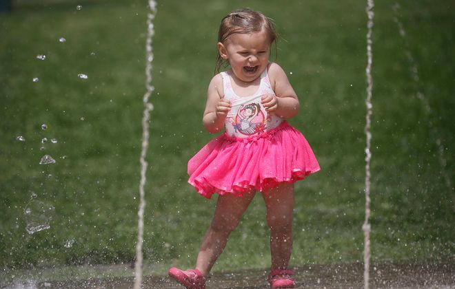 Two-year-old Nora Kessel reacts as she runs through the water in the Cazenovia Park Splash Pad. (Derek Gee/Buffalo News)