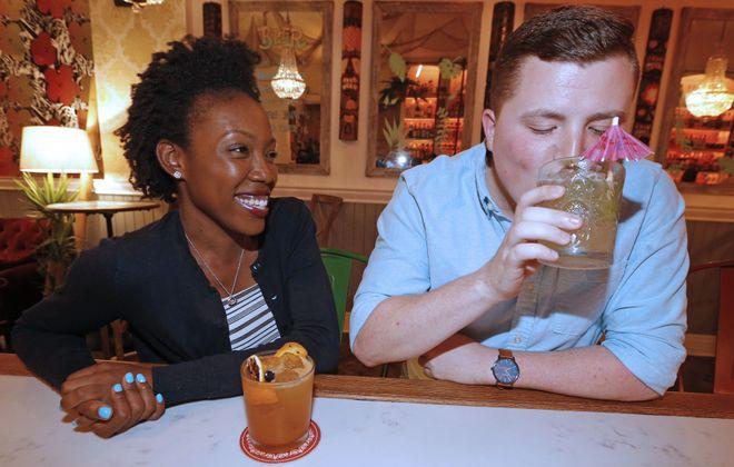 Kadijah McKenzie, left, enjoys a Cobra's Fang cocktail while watching Connor Brown sip a vintage drink that originated in Cairo, Egypt. (Robert Kirkham/Buffalo News)