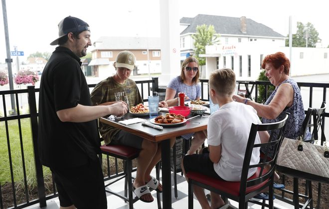 The renovated Imperial Pizza in South Buffalo now includes an expansive patio.  Waiter Patrick Lawler serves Colin Bagwell, left, his mother Molly, great aunt Colleen Sheehan and brother Liam Bagwell who were visiting from Charlotte, North Carolina. (Sharon Cantillon/Buffalo News)