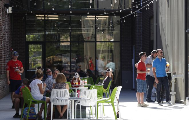 Customers hang out in the outdoor beer garden at Resurgence Brewing Company. (Sharon Cantillon/News file photo)