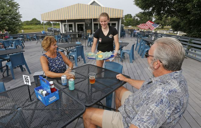 Lumberjack's server Bridget Wilson delivers a fried bologna sandwich and a cheeseburger to a couple on the patio. (Robert Kirkham/Buffalo News)