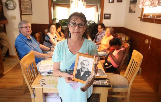 "Celeste LeClair-Coleman, whose passion may lead to a monument for three men killed while building the Skyway, holds a picture of her father, Mohawk ironworker Mitch LeClair. Behind her, from left: Mark Weber, whose great-uncle, Daniel Smith, died when he fell from the span; LeClair-Coleman's sisters, Florence ""Mickie"" Golba and June Mafhoud; Ron Coleman, LeClair-Coleman's husband; Patricia White Hancock and her sister, Jaqueline White Gibson, whose brother Gatlin White also died in a Skyway fall; and Gibson's granddaughter, Elizabeth Keys, 10.  (John Hickey/Buffalo News)"