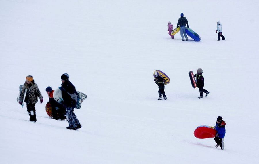 Tubers walk up the hill at Elma Meadows Golf Course during a winter day. The hill was the location of a sledding accident that led to a lawsuit. (Robert Kirkham/ News file photo)