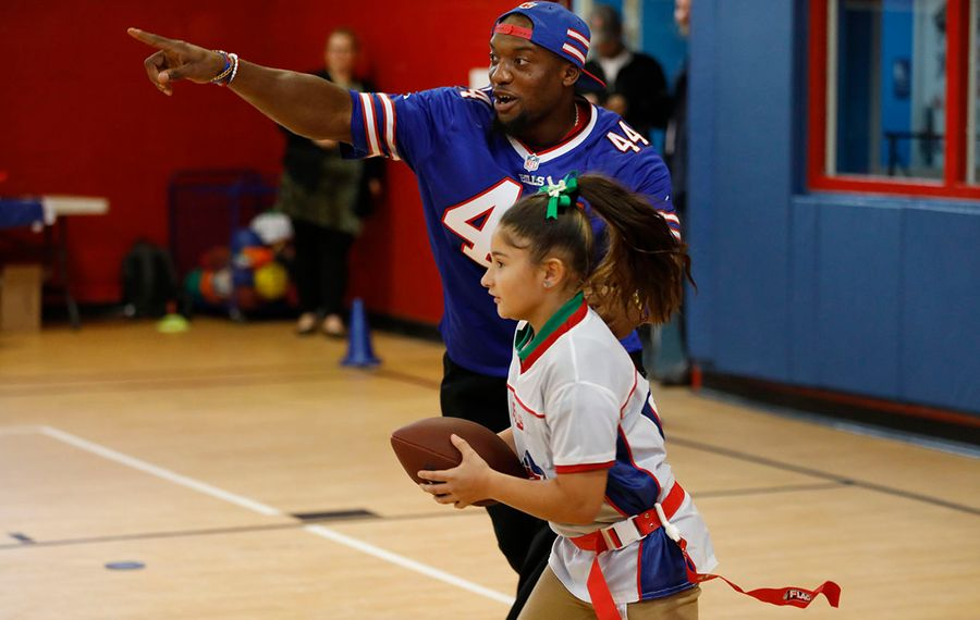 Buffalo Bills linebacker Deon Lacey plays flag football with Eliani Gonzalez in the after-school program at the Boys & Girls Club Butler-Mitchell Clubhouse in 2018. (Derek Gee/News file photo)