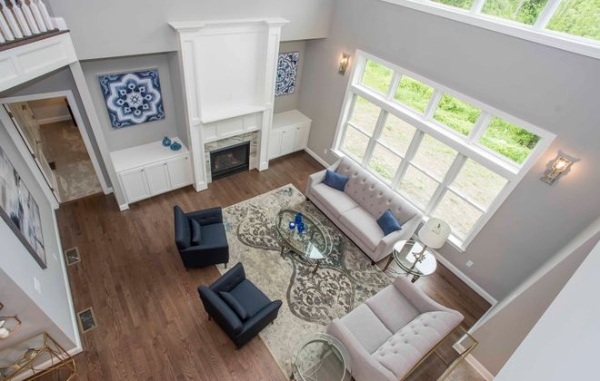 The two story great room features a gas fireplace and built in cabinets.