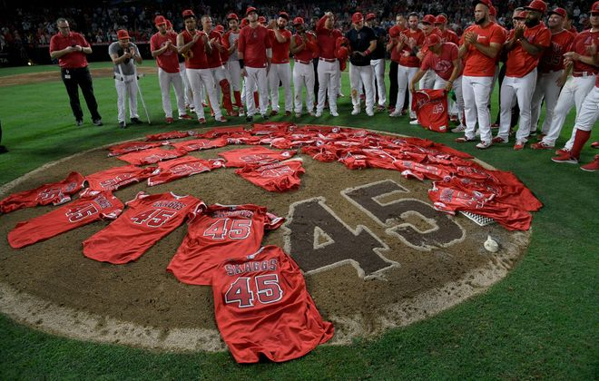 Los Angeles Angels players join in a round of applause for late teammate Tyler Skaggs after laying their jerseys on the mound following Friday night's combined no-hitter against Seattle (Getty Images).
