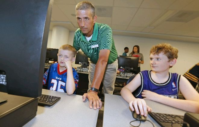 WNY STEM Hub teacher Dan Thomas works with Zachary Kelkenberg, 12, , left, and Brendan Burd, 11, on an animated video project as the Institute for Autism Research at Canisius College incorporates STEM into its summer program. (Robert Kirkham/Buffalo News)