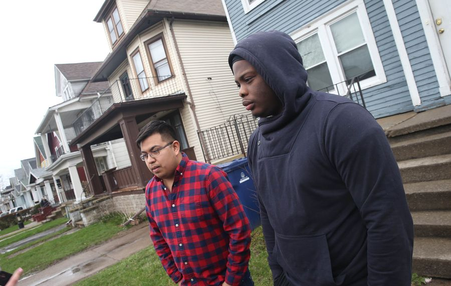 Neighbors Adam Rodriguez, left, and Lavontae Armwood,talk about what they witnessed last night, of a student brought out between houses and police and rescue personel working on passed out male bin driveway between their house and yellow fraternity house, it left a student hospitalized from a hazing incident at Sigma Pi fraternity, fraternity was shut down at 69 Custer, in Buffalo, on Friday, April 12, 2019.   (John Hickey/Buffalo News)