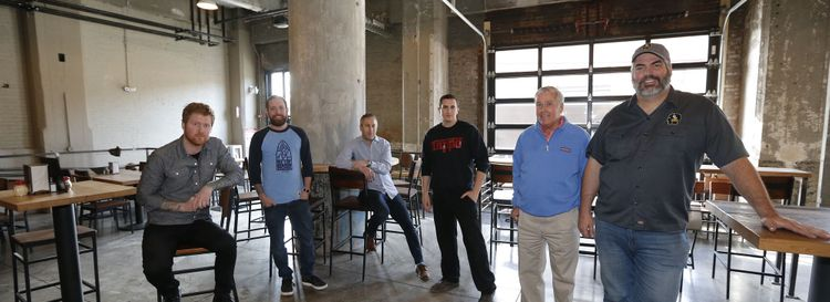 The Thin Man Brewery Chandler Street team, from left, is Josh Mullin, marketing director; Jack McAuliffe, general manager; Ben Siegel, head designer; Phil Limina, chef and co-owner of Tappo; developer Rocco Termini; and Mike Shatzel, Thin Man owner. (Robert Kirkham/Buffalo News)