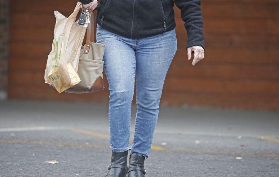 A shopper carries a plastic grocery bag after shopping at Wegmans on Transit Road in Depew. (Robert Kirkham/Buffalo News)