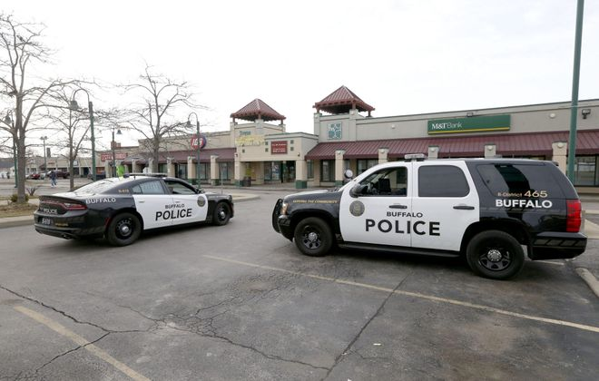 Police officers were parked in the Towne Gardens shopping plaza on William Street in Buffalo on April 7, 2019, the day after a stray bullet killed 12-year-old Badraldeen Mohamad Elwaseem in a nearby apartment. (Robert Kirkham/Buffalo News)