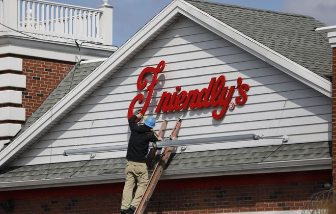 A worker removes the Friendly's sign from above the restaurant on Maple Road in Amherst. (Derek Gee/Buffalo News)