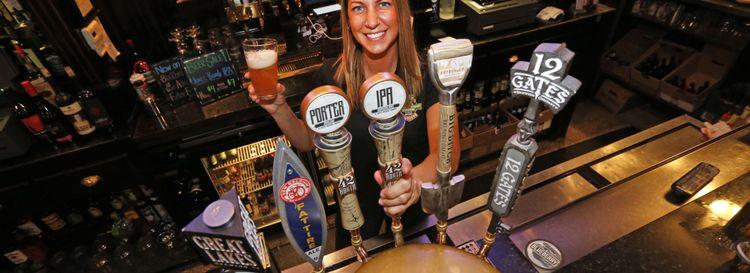 Bartender Candice Kulikowski pours a 42 North IPA at Riley Street Station in East Aurora. (Robert Kirkham/Buffalo News)