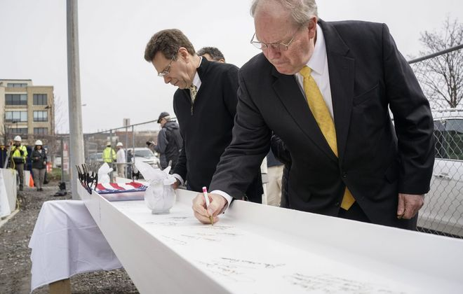 Buffalo City Mission CEO and Executive Director Stuart Harper signs the final steel beam before it is lifted in place on the new community center under construction at the Buffalo City Mission on Tuesday, April 16, 2019. (Derek Gee/Buffalo News)