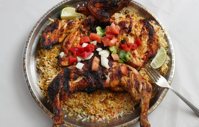 Almandi Restaurant's whole grilled chicken, served on a bed of rice. (Sharon Cantillon/Buffalo News)