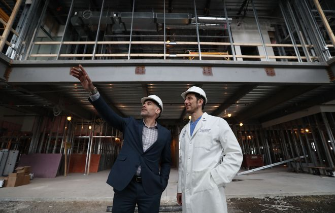 Michael Cournyea, CEO of UB Neurosurgery, left, and Dr. Elad Levy, president of UBNS, and professor and chairman of neurosurgery in the Jacobs School of Medicine and Biomedical Sciences, stand in front of the future lobby of the UBNS Comprehensive Neuroscience Center.(Sharon Cantillon/Buffalo News)