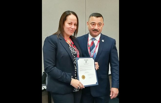The deputy mayor of Dunkerque, France, Karima Benarap, presents Dunkirk Mayor Willie Rosas with a medal and proclamation last week during a ceremony at the French Embassy in Washington D.C. (Image courtesy of the French Embassy)