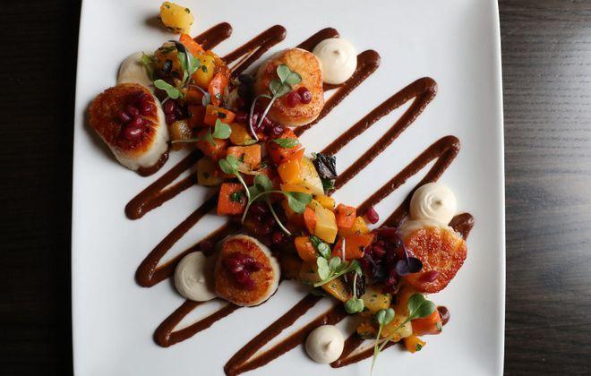Farmer's Creekside Tavern's day boat scallops come with Fresno chile mole and pomegranate.  (Sharon Cantillon/Buffalo News)