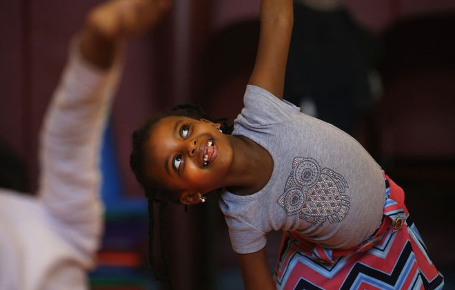 Yoga is helping kids across the region in a variety of ways. Bella Rezene, 7, is among them. The Bennett Park Montessori School first-grader takes a weekly Yogis in Service after-school yoga class.  (Robert Kirkham/Buffalo News)