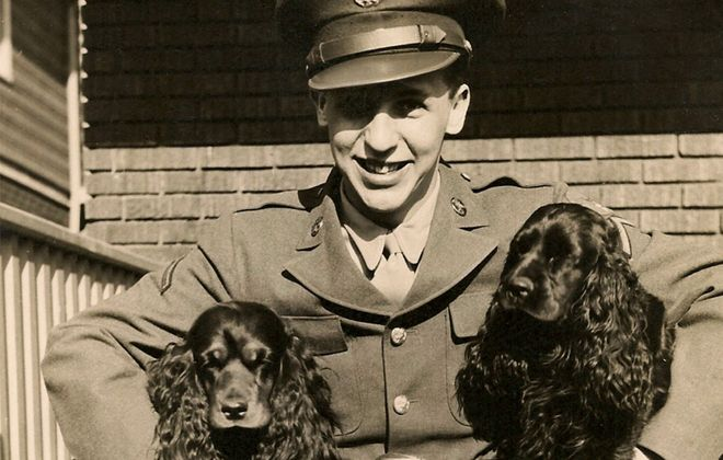 """Vince Rogers Jr., on a visit with his parents in Snyder during World War II, embraces """"the girls,"""" Melody and Music, the family dogs. (Image courtesy of March Field Air Museum)"""