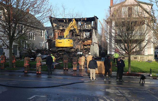 Buffalo fire crews and investigators stand by as multiunit house is demolished after an overnight fire on Elmwood Avenue, in Buffalo, on Wednesday, May 8, 2019. (John Hickey/Buffalo News)