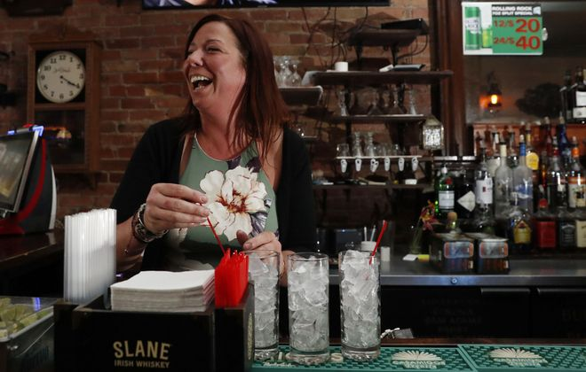 Alley Cat bartender Amanda Markovich laughs with customers as she makes a few gin and tonics. (Sharon Cantillon/Buffalo News)