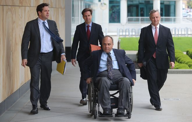 Rochester developer Robert C. Morgan, center, arrives at Robert H. Jackson United States Courthouse for an appearance in May. (John Hickey/News file photo)