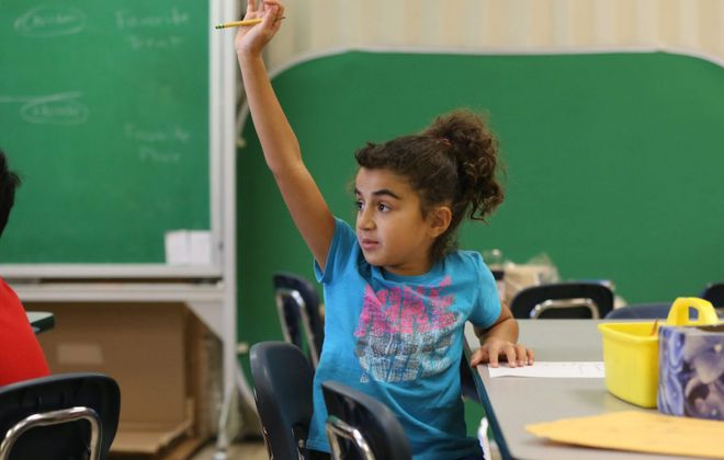 Lauren Riad, 9, raises her hand during class at Country Parkway Elementary School in Williamsville. (Derek Gee/Buffalo News)