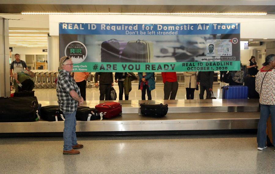 Travelers pick up their baggage at the Buffalo Niagara Airport, where a new banner hangs to promote awareness about the need to upgrade to a REAL ID in order to board any commercial starting October of next year.  (John Hickey/Buffalo News)