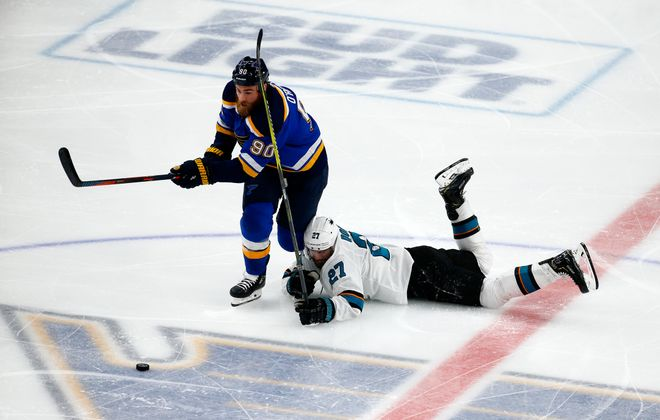 Joonas Donskoi of the San Jose Sharks falls to the ice against Ryan O'Reilly of the St. Louis Blues (Dilip Vishwanat/Getty Images)