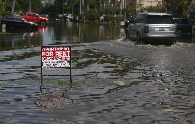 An apartment for rent sign is seen in a flooded street caused by the combination of the lunar orbit which caused seasonal high tides and what many believe is the rising sea levels due to climate change in 2015 in Fort Lauderdale, Fla.  South Florida is projected to continue to feel the effects of climate change and many of the cities have begun programs such as installing pumps or building up sea walls to try and combat the rising oceans.  (Getty Images file photo)