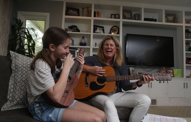 """Brigid Maloney, co-leader with the Lippes Mathias Wexler Friedman firm's Health Law Practice, plays guitar and sings with her daughter, Kate, 9, at their home in East Aurora, """"We want to raise kids that are healthy, kind, open-minded and academically conscientious. Everything has to feed into that,"""" she says. (John Hickey/Buffalo News)"""