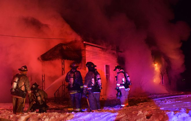 Buffalo firefighters try to put out a fire at 38 Hirschbeck St. on March 17, 2017. Six days later, the body of Dana Gidney, a homeless former Marine who was squatting in the house, was found in the rubble. (Donald Kilianski/Special to The News)