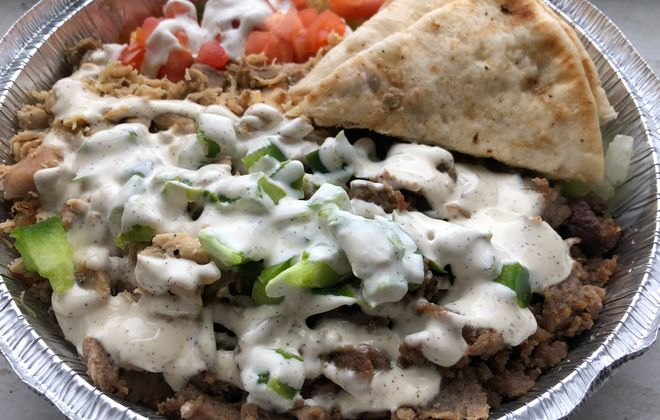 The Combo Platter - the most popular item at The Halal Guys - includes both chicken and gyro, freshly shaved off of a spit. (Ben Tsujimoto/Buffalo News)
