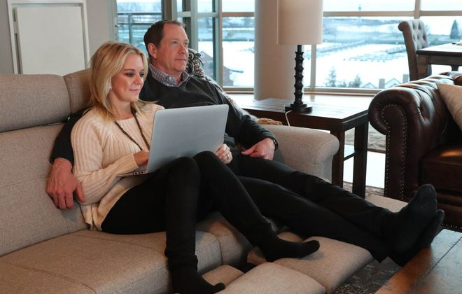 Phil and Karin Housley relax on a loveseat in their lakefront condo, which they sold Wednesday for $710,000. (Sharon Cantillon/Buffalo News file photo)