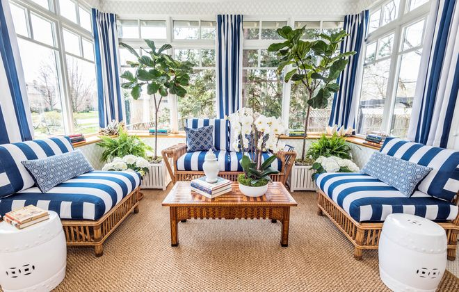 Bold blue-and-white stripped window treatments bring just the right amount of definition into the sunroom's great expanse of glass while keeping the room drenched in light. (Matthew Digati)