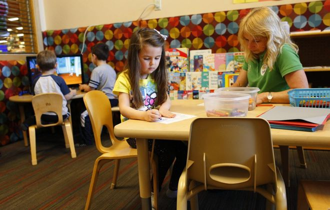 Harper Adams, 5, works on a craft project with with Kathy Rosiek as her brothers play video games in the Wkids room at the Alberta Drive Wegmans. The chain is closing the Wkids in-store child care room, the last one in Buffalo Niagara, on June 2.. (Derek Gee/Buffalo News)