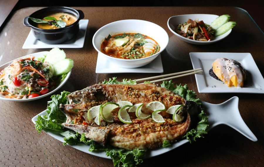 Lin Restaurant spread includes, from top left, panang Thai curry, mohinga fish soup, crispy pork belly, mango sticky rice, crispy fish, and garlic noodles. (Sharon Cantillon/Buffalo News)