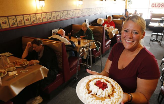 Waitress Robin Santarini-Soto holds up the strawberry waffle with whipped cream at Londa's Diner in Depew. (Derek Gee/Buffalo News)