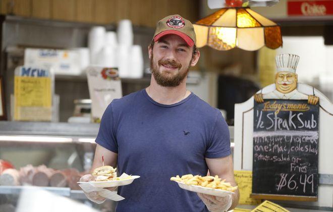 Joe Hatley serves a turkey sub and fries at Mayback's Deli on Niagara Falls Boulevard. (Mark Mulville/Buffalo News)