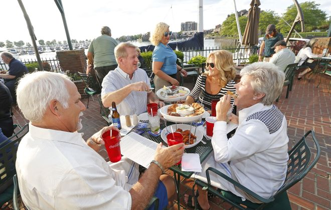 Enjoying cocktails, oysters and wings are from left, Charlie Maclay of Williamsville, Brian McGrath of Clarence, and their wives Kim McGrath and Darlene Maclay, on the patio. (Robert Kirkham/Buffalo News)